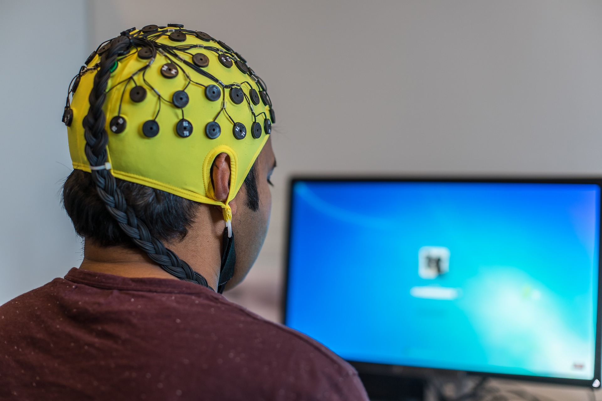 Man sitting at computer, wearing an EEG cap